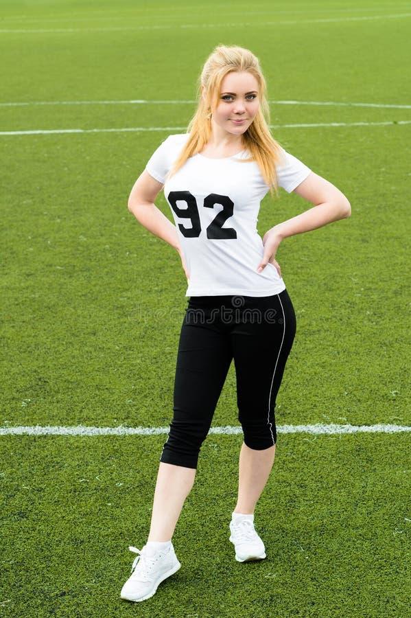 Sportkvinna som står full längd på fotbollfält för grönt gräs royaltyfri foto