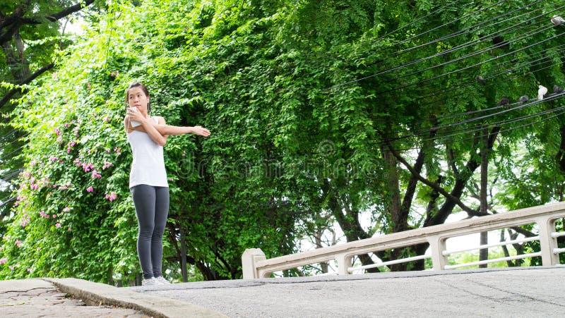 Sportkvinna som sträcker att köra i gatan stads- Park City royaltyfri fotografi