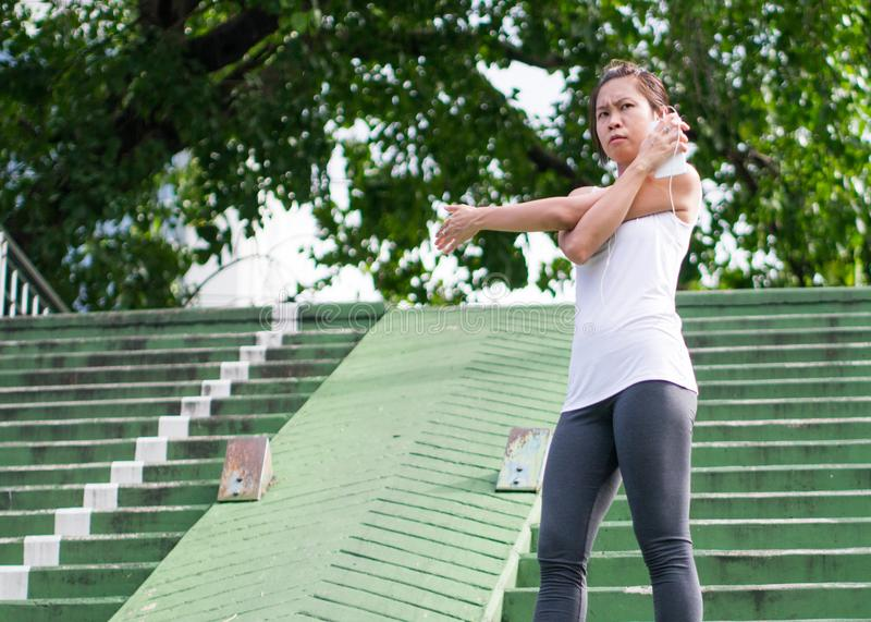 Sportkvinna som sträcker att köra i gataPark City stads- bakgrund royaltyfria foton
