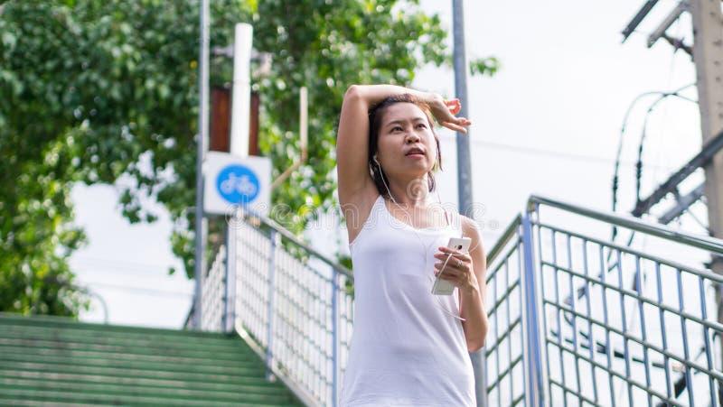 Sportkvinna som sträcker att köra i gataPark City stads- bakgrund arkivfoto