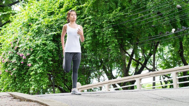 Sportkvinna som sträcker att köra i gataPark City stads- bakgrund fotografering för bildbyråer