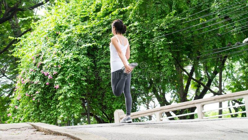 Sportkvinna som sträcker att köra i gataPark City stads- bakgrund arkivbilder