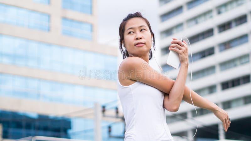 Sportkvinna som sträcker att köra i stads- byggnad för stad arkivbilder