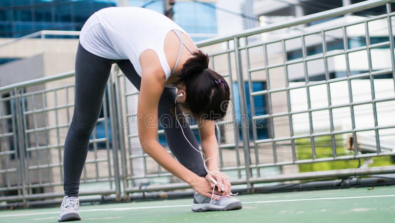 Sportkvinna som sträcker att köra i stads- byggnad för stad royaltyfri fotografi