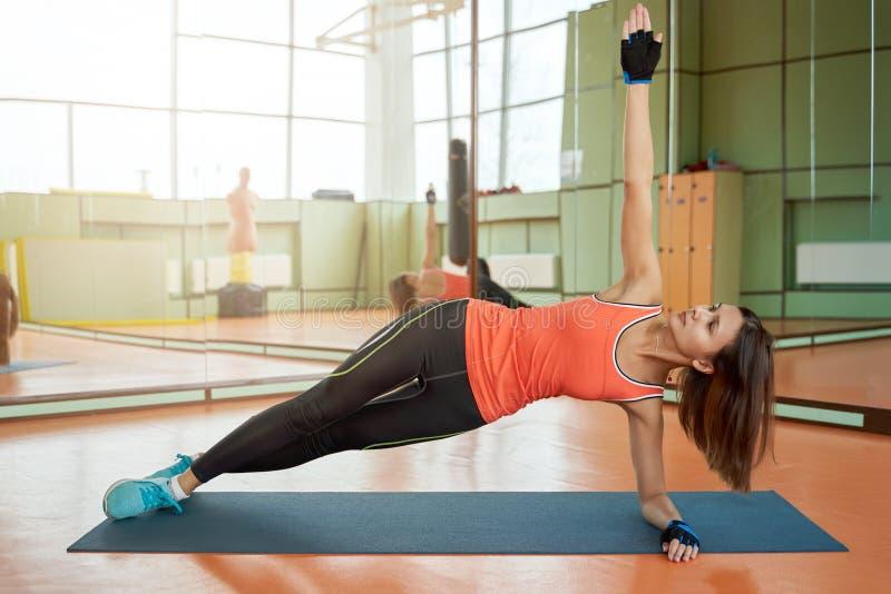 Sportkvinnaanseendet i poserar av stången på armbågen, lyfter upp handen, sträcker den hela kroppen till taket royaltyfria foton