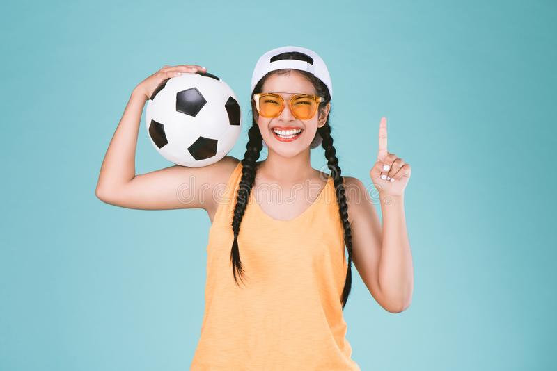 Sportkvinnafan som rymmer en fotbollboll som firar fingret för punkt en upp vinnaretecken arkivfoton