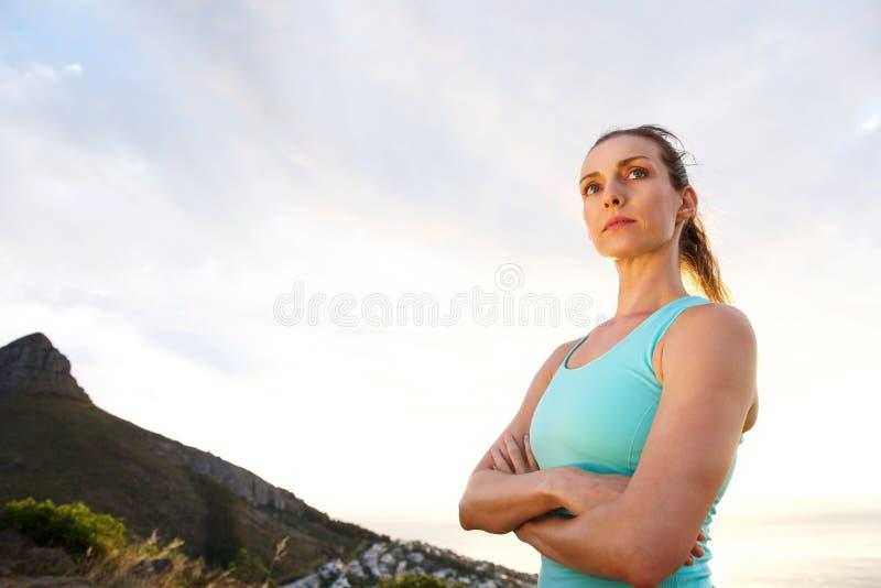Sportkvinnan med armar korsade att stirra royaltyfri fotografi