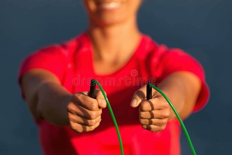 Sportkvinnan rymmer ett överhopprep i hans händer kopplas in i gymnastik mot arkivfoto