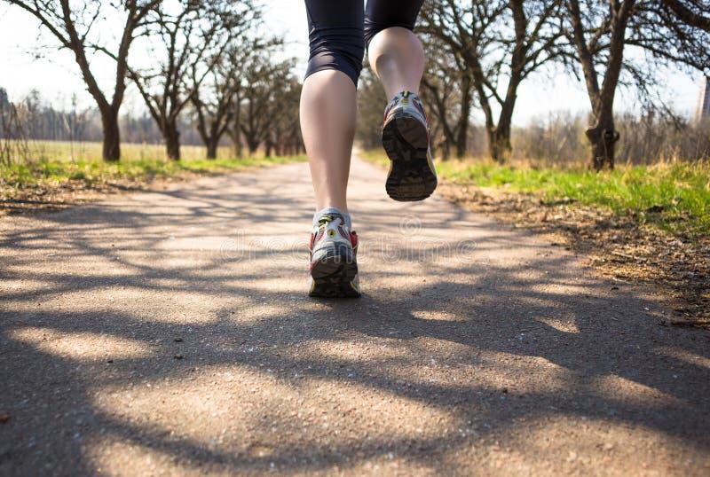Sportkvinnan som joggar utanför i vår, parkerar otta royaltyfri bild