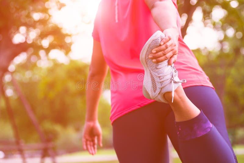 Sportkvinnan som sträcker benmuskeln som förbereder sig för att köra i allmänheten, parkerar utomhus- Stäng sig upp av att göra f royaltyfria foton