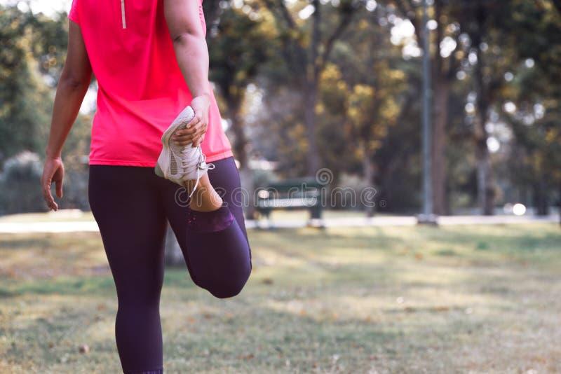 Sportkvinnan som sträcker benmuskeln som förbereder sig för att köra i allmänheten, parkerar utomhus- Stäng sig upp av att göra f royaltyfria bilder