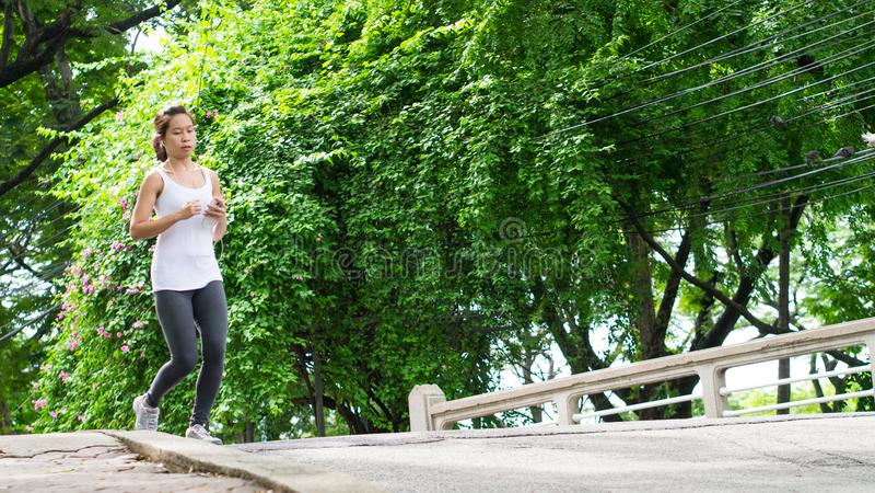 Sportkvinnaspring i gataPark City stads- bakgrund fotografering för bildbyråer