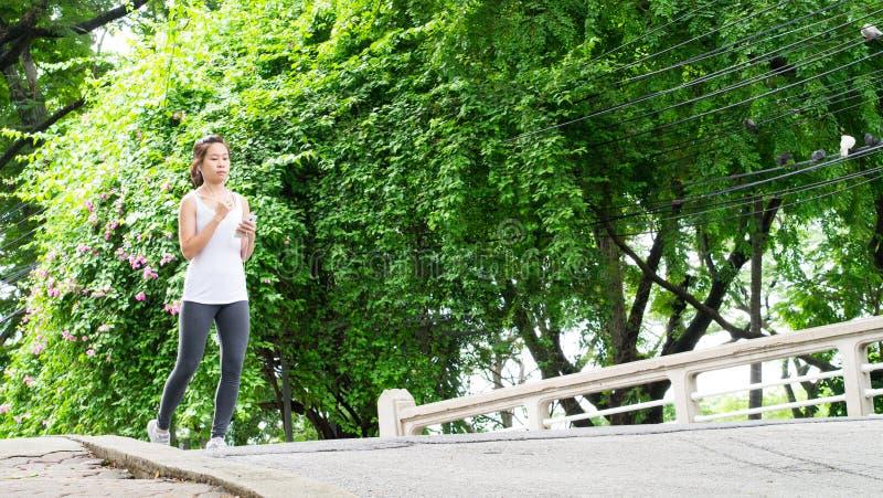 Sportkvinnaspring i gataPark City stads- bakgrund arkivfoton