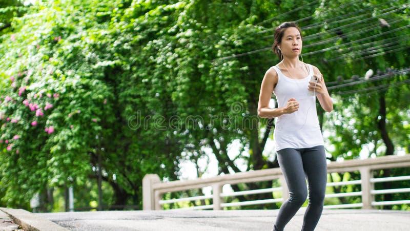 Sportkvinnaspring i gataPark City stads- bakgrund arkivbilder