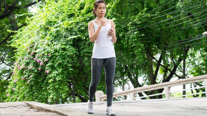 Sportkvinnaspring i gataPark City stads- bakgrund royaltyfri foto