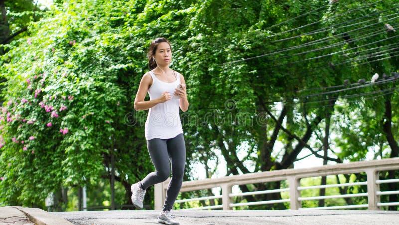 Sportkvinnaspring i gataPark City stads- bakgrund royaltyfria foton