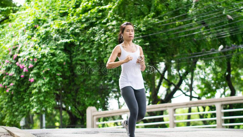 Sportkvinnaspring i gataPark City stads- bakgrund royaltyfria bilder