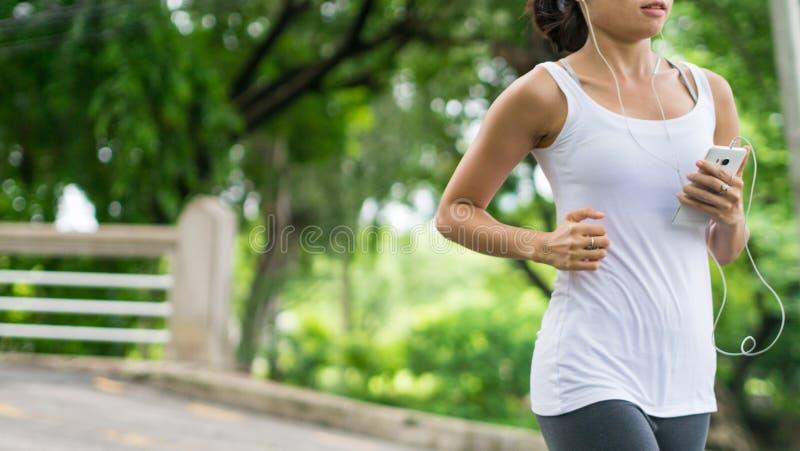 Sportkvinnaspring i gataPark City stads- bakgrund royaltyfri fotografi