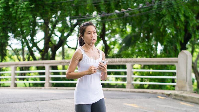 Sportkvinnaspring i gataPark City stads- bakgrund arkivfoto