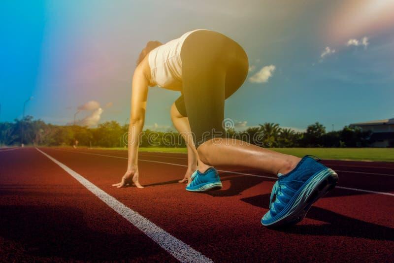 Sportlöparekvinna på stadionspår arkivfoto