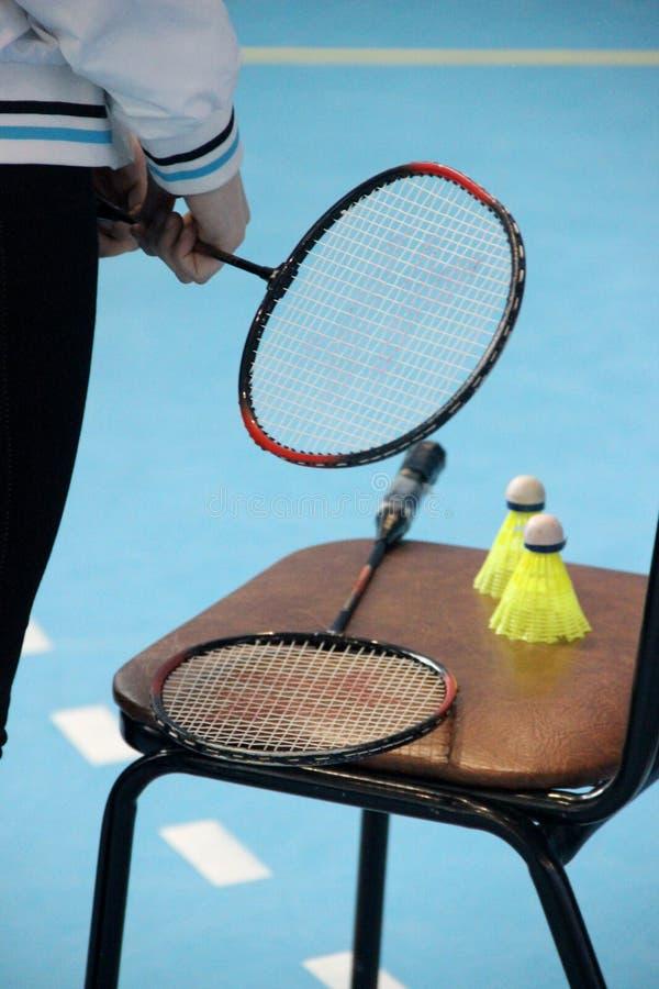 Sportlekar och konkurrenser Tonårs- rymmer en badmintonracket med hennes fingrar, två fjäderbollar, racket på en stol royaltyfri fotografi