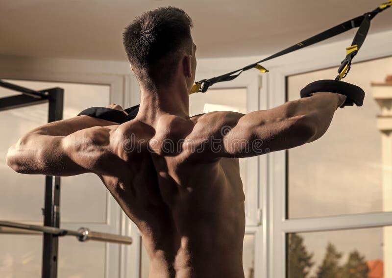Sportler, Athlet, muskulöser Macho trainiert mit trx Schleifen, Fenster auf Hintergrund, Abschluss oben Mann mit dem nackten Tors stockfotografie