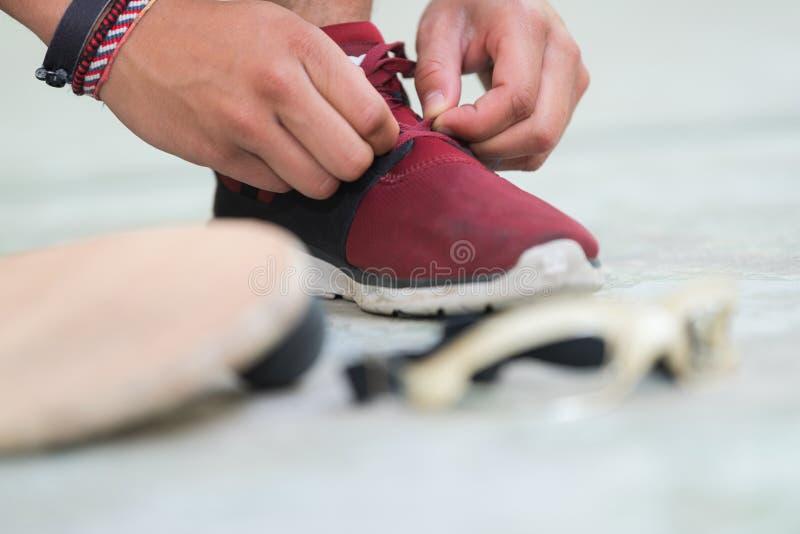 Sportler, der die Schuhe neben der Augenbraue und dem Ball justiert lizenzfreie stockfotografie