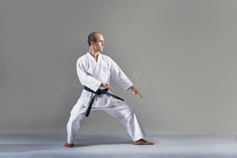 Sportler in einem weißen karategi führt eine formale Karateübung durch lizenzfreie stockbilder
