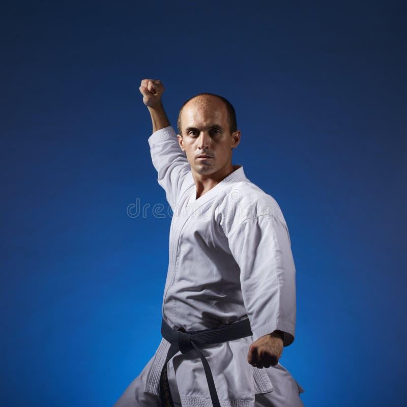 Sportler führt formale Übungen von Karate auf einem blauen Hintergrund durch stockbild