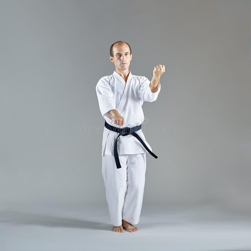 Sportler im karategi und mit einem schwarzen Gürtel führt eine formale Karateübung durch stockfoto