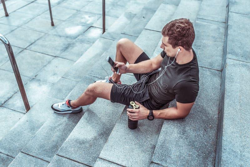 Sportler ruhen im Sommer auf Treppenaufgang Trainieren Sie nach dem Training mit Fitness und Outdoor-Training Handy lizenzfreies stockfoto