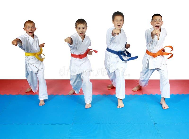 Sportler vier im karategi und mit Gurten schlagen Schlaghände stockbilder