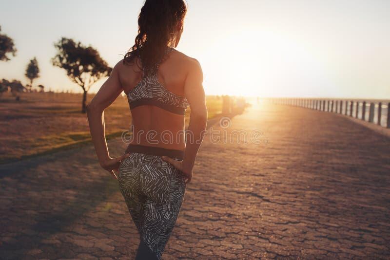 Sportlerin, die auf eine Küstenpromenade bei Sonnenuntergang geht stockfoto