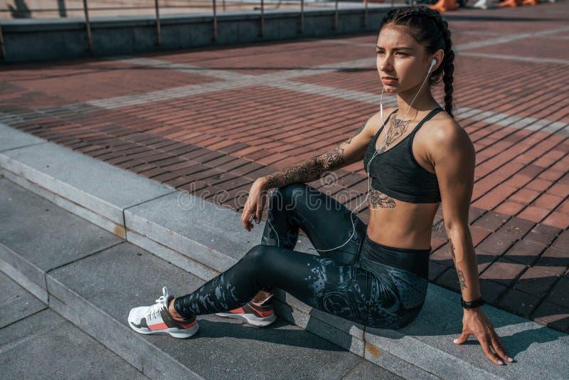 Sportlerin, die nach Sommertrainingsstadt stillsteht Kopfh?rer rufen Online-Bewerbungs-Musiksoziale netzwerke an Konzept stockfotografie