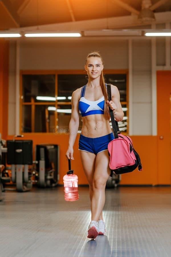 Sportlerin, welche die Aufstellung mit Flasche des Wassers und der Sporttasche in der Turnhalle aus?bt Trainingseignungskonzept lizenzfreie stockfotos