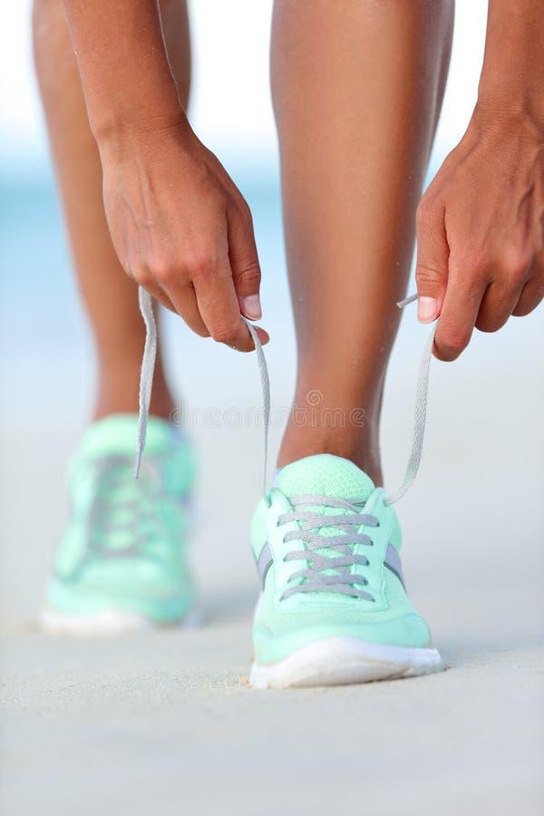 Sportlerinläufer, der bereite Bindungslaufschuhe auf Strand erhält lizenzfreie stockfotografie