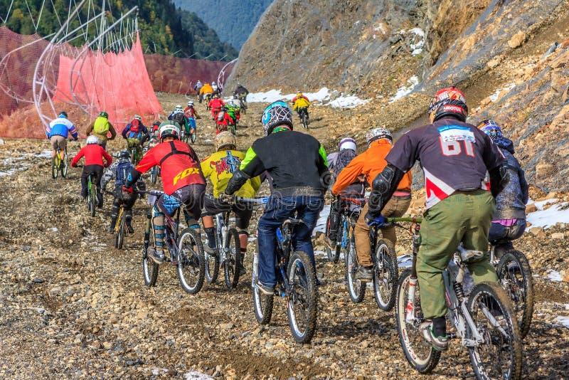 Sportlermountainbiker reiten Fahrräder beim Laufen hinunter Skibahn im Kaukasus stockfoto