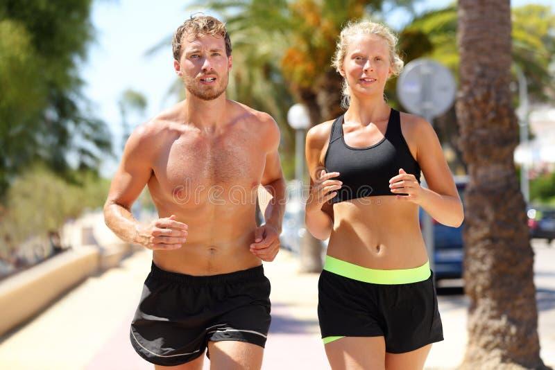 Sportleute - aktive Paare, die in Stadt laufen stockfoto