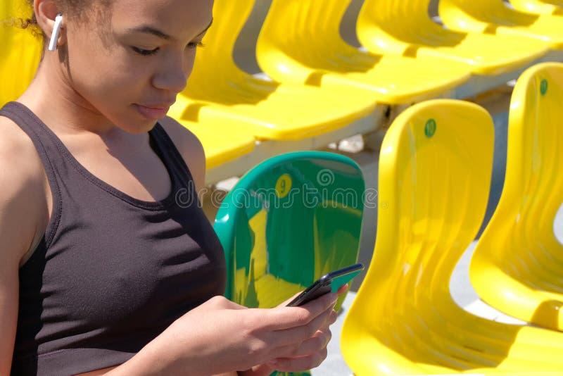 Sportlevensstijl Een sexy Afrikaans Amerikaans meisje in een zwarte T-shirt met een witte draadloze oortelefoon in haar oor onder royalty-vrije stock foto
