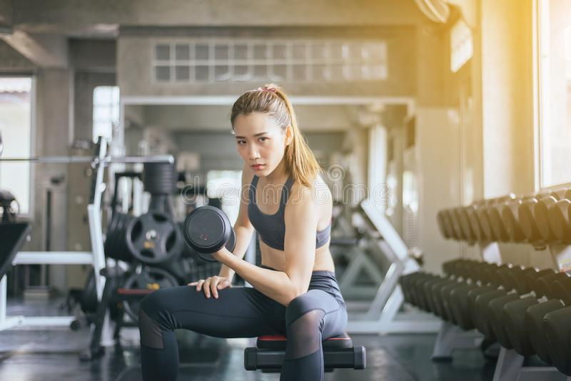 Sportliche überzeugte Frauenübung mit den Dummköpfen, die in der Sportkleidung weiblich sind, tut die Übungen an der Turnhalle lizenzfreie stockbilder