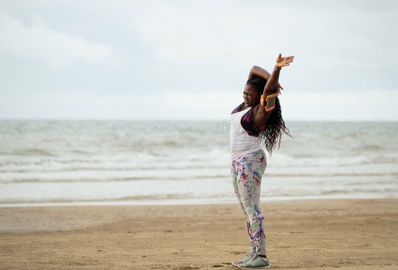 Sportliche afrikanische Frau, die Übungen auf dem Strand unter dem Regen tut lizenzfreie stockfotos