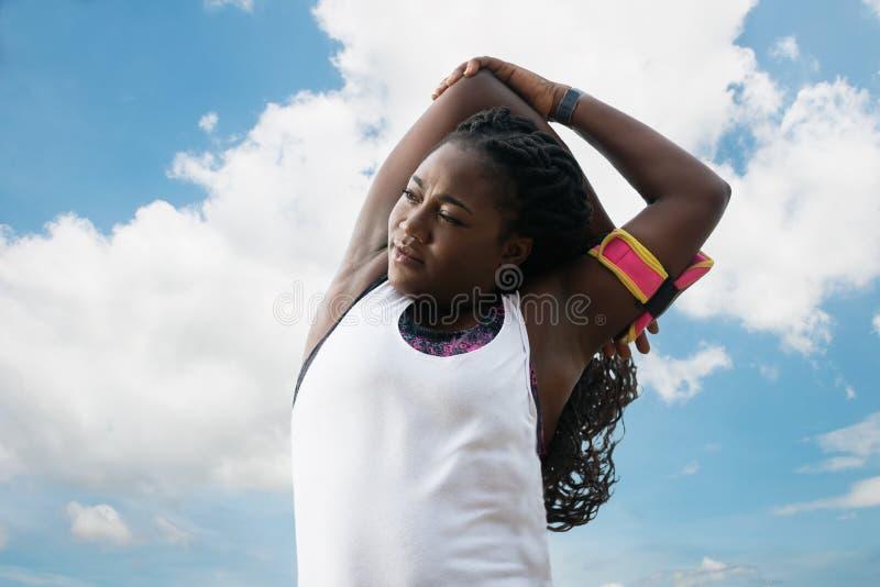 Sportliche attraktive afrikanische Frau, die Übung über Hintergrund des blauen Himmels tut stockfotos