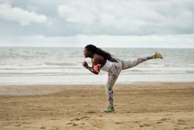 Sportliche attraktive afrikanische Frau, die Übung unter Regen tut lizenzfreies stockbild