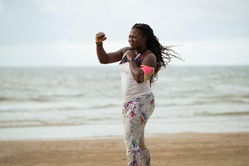 Sportliche attraktive afrikanische Frau, die Übungen auf dem Strand tut stockbilder