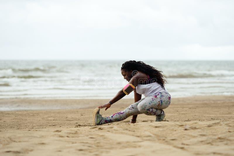 Sportliche attraktive afrikanische Frau, die Übungen auf dem Strand tut stockfoto