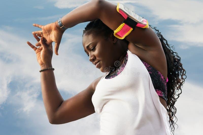 Sportliche attraktive afrikanische Frau, die Übungen tut stockbild