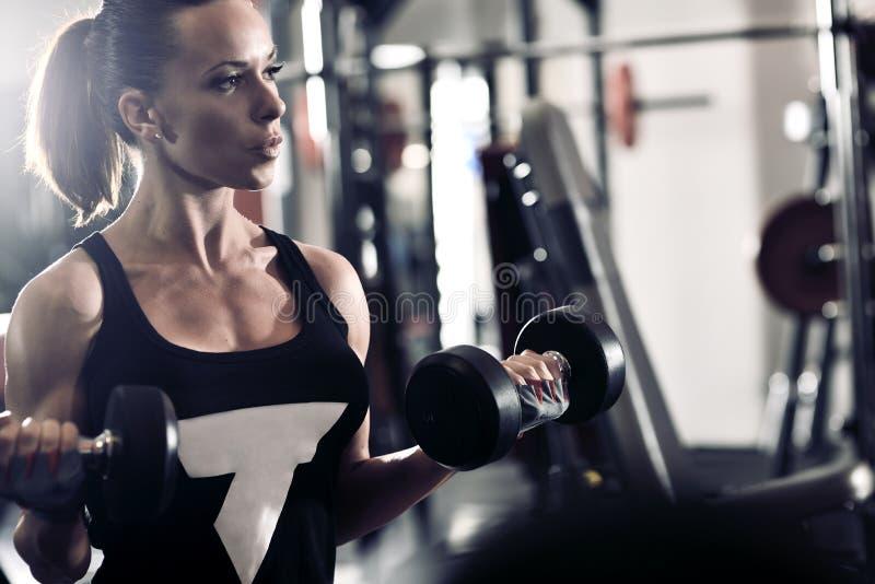 Sportliche attraktive Frau in der Turnhalle mit Übungsausrüstung stockfotografie