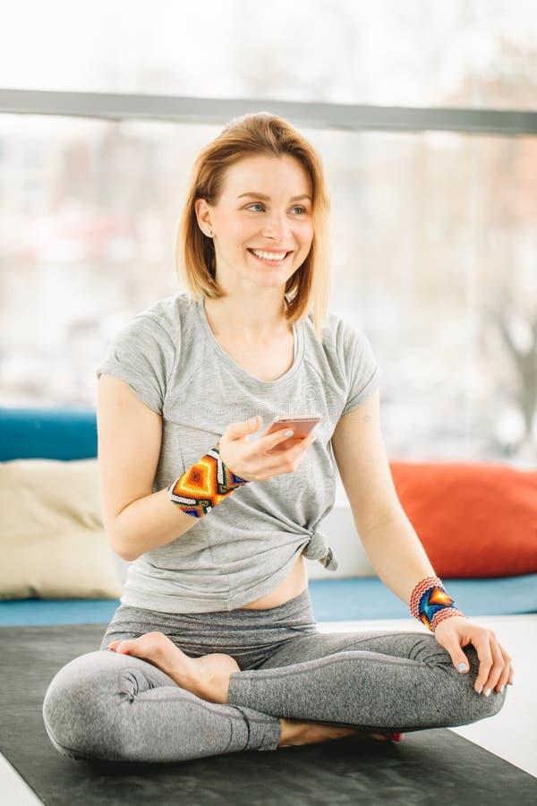 Sportliche attraktive Frau, die in Lotus-Haltung sitzt stockbilder