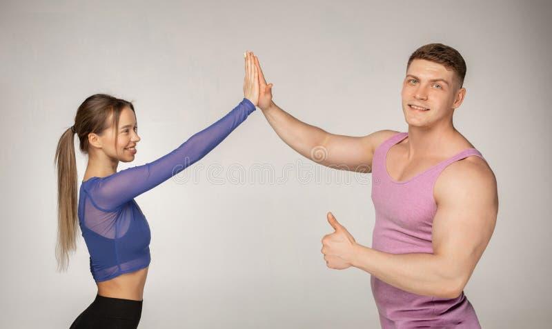 Sportliche attraktive Paare in der modischen Sportkleidung, die miteinander hohe fünf gibt stockbild