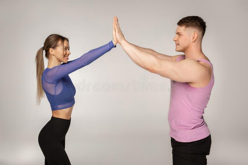 Sportliche attraktive Paare in der modischen Sportkleidung, die miteinander hohe fünf gibt lizenzfreies stockbild